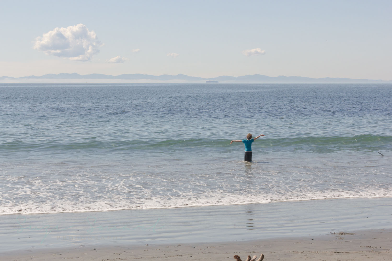 Child running into Pacific Ocean